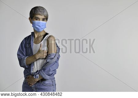 Happy Middle Aged Asian Woman Vaccinated Showing Thumbs Up At Adhesive Plaster Bandage On Her Arm Af