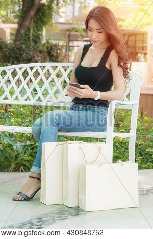 Woman Sitting With A Shopping Bag.