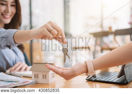 Client Taking Keys From Female Real Estate Agent During Meeting After Signing Rental Lease Contract