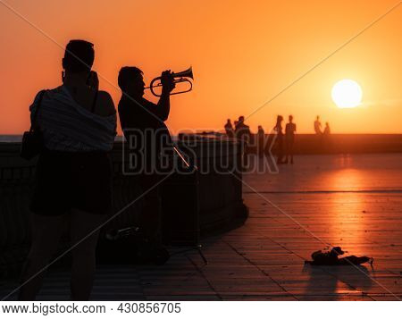 Livorno, Italy - July 2021: Silhouette Of A Lone Trumpeter Playing His Trumpet At Sunset In A Public
