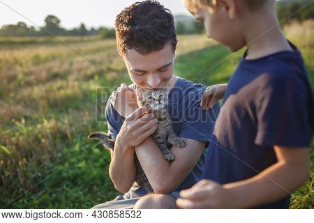 Young Guy Found And Picked Up Little Stripped Kitten During Walking In The Field And Going To Home I