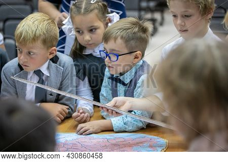 A First Grader With Glasses Examines A Map In The Lesson. September 1. School.