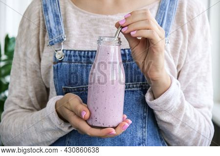 Female Hands Holding Blueberry Smoothie Topped With Blueberries. Woman Eating Glass Of Breakfast Pro