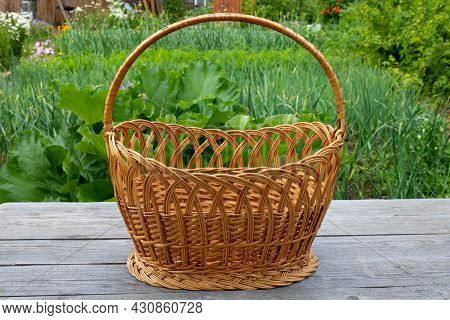 A Large Wicker Basket On A Gray Table Against A Background Of Green Grass.picnic Basket