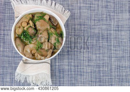 Marinated Mushrooms In A White Ceramic Bowl With Dill. The White Ethnic Fringed Napkin On A Blue Tab