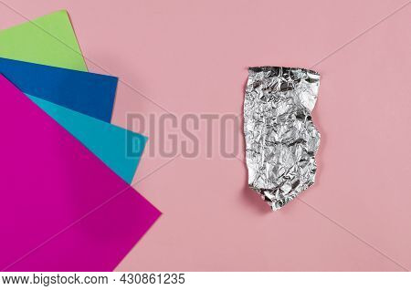 Minimalist Composition With Crumpled Foil And Multicolored Paper Against A Pink Background. A Piece