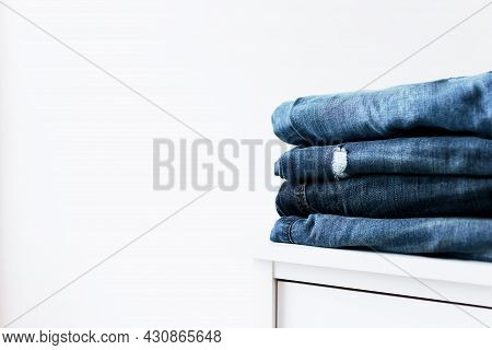 Stack Of Different Blue Denim Jeans Trousers On The Shelf Or Table. Photo Of Stacked Various Shade J