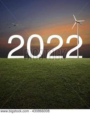 2022 White Text With Wind Turbine On Green Grass Field Over Sunset Sky, Happy New Year 2022 Ecologic
