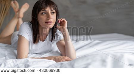 Portrait Of A Young Brunette Woman Lying On The Bed In The Bedroom. Girl On White Bed Linen. Happy M