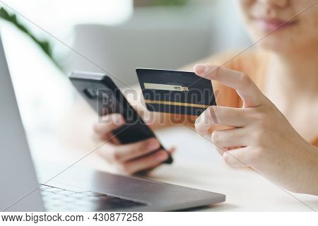 Young Woman Holding Credit Card And Using Smart Phone For Online Shopping, Internet Banking, E-comme