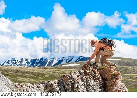 Man Hiker Or Climber Walks Along The Top Of The Mountain Overlooking The Valley Of The Mountains. Tr