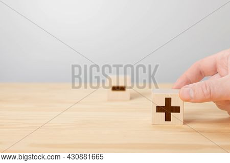 Person Holding Plus Sign Block Against Minus. Plus Or Minus. Man Hold Cube With Plus Icon. Hand Choo