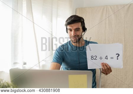 Distance Education. Handsome Man Teacher With Headset Showing Blank Paper Sheet For Teaching Online