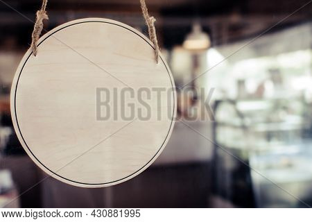 Empty Wooden Sign Board Hanging On Glass Door With Sun Light In Modern Cafe Restaurant, Copy Space F