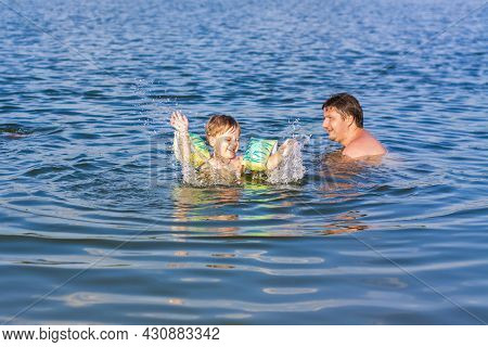 A Family, A Father And His Sons Are Swimming In The River On A Very Hot Summer Day. Swim In Reservoi