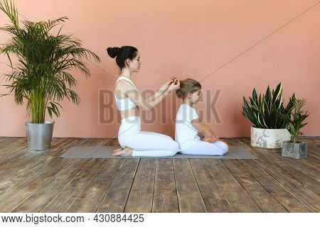 Young Blonde Girl Getting Her Long Hair Braided By Mother Before Sport Training While Sitting On Flo
