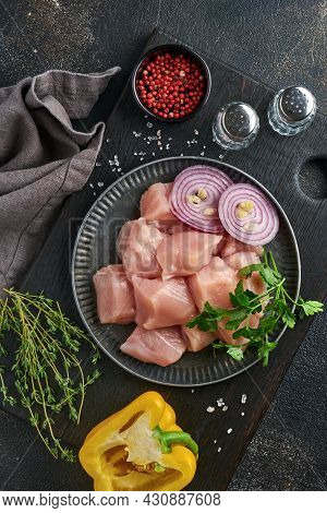 Raw Pieces Meat Ingredients Of Chicken On Wooden Board, Spices, Herbs And Vegetables On Dark Grey Ba