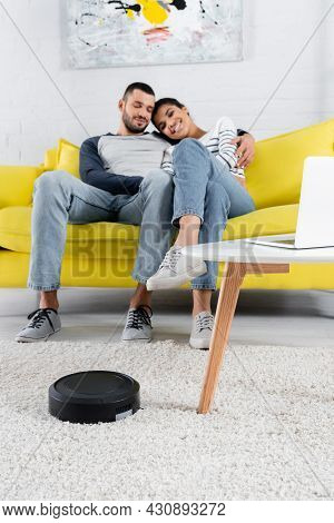 Robotic Vacuum Cleaner Near Laptop And Smiling Multiethnic Couple On Couch