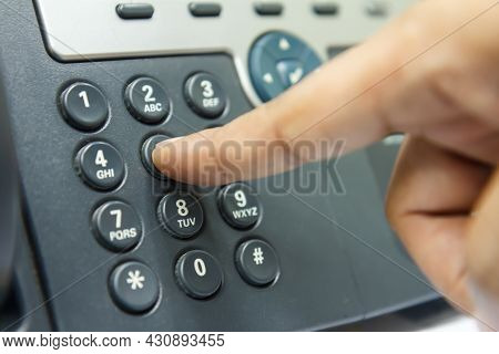 Closeup Of Man Hand While Dialing A Telephone Number To Make A Call Customer/contact And Customer Se