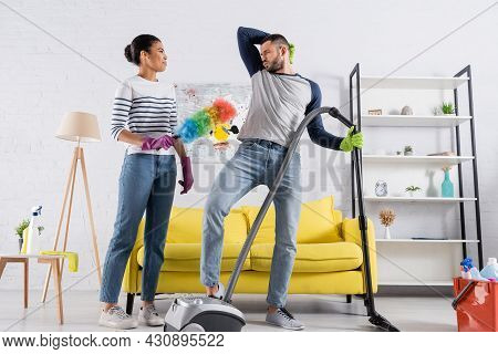 African American Woman With Dust Brush Looking At Boyfriend With Vacuum Cleaner Grimacing At Home