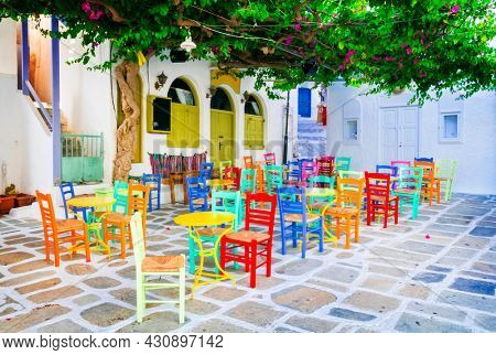 Traditional Greek taverns on the streets. Ios island, old town Chora. Restaurant with colorful typical chairs. Cyclades, Greece