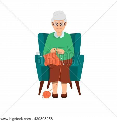 Grandma Sits In A Soft Blue Chair And Knits. Grandmother With Glasses. A Ball Of Wool. Needlework, P