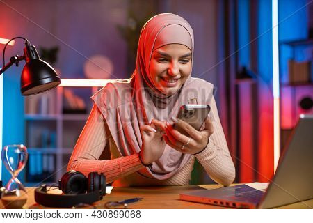 Attractive Arabian Woman Texting On Modern Smartphone While Sitting At Desk With Wireless Laptop. Pr