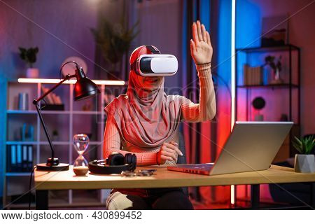 Young Arabian Woman Sitting At Home Office And Using Vr Headset And Laptop For Work During Evening T