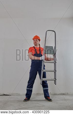 A Satisfied Man In A Helmet Looks Through The Ladder