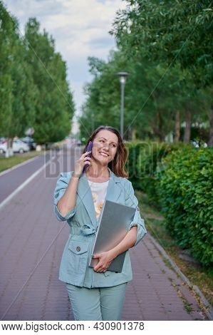A Cheerful Girl Walking Around The City With A Laptop