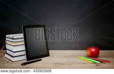 Online education - Books and tablet on the desktop on blackboard background, copy space for text