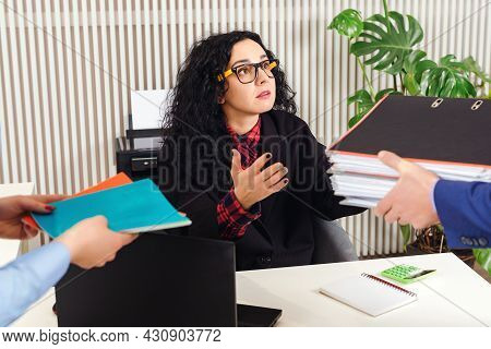 Businesswoman With A Lot Of Work At Workplace. Unfair Chief Giving Assistant Papers And Documents. S
