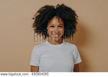 Portrait Of Happy Young African Woman With Broad Shining Smile Dressed In White Tshirt Posing Alone