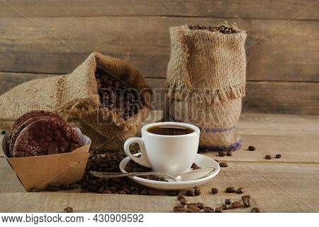 A Cup Of Coffee. A Sack Of Coffee On A Wooden Background, Hot And Fresh Morning Coffee. Fresh Coffee