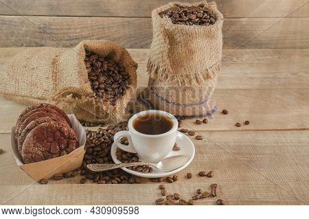 A Cup Of Coffee. A Sack Of Coffee On A Wooden Background, Hot And Fresh Morning Coffee. Copyspace