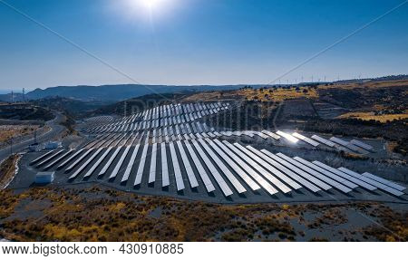 Photovoltaic Panels Of Solar Power Station On A Hill. Aerial Landscape