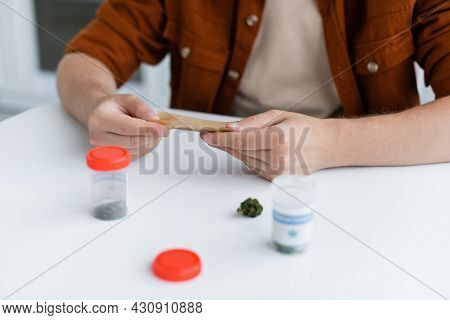 Partial View Of Sick Man Making Joint With Medical Hemp Near Containers On Table