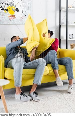 Multiethnic Couple Pillow Fighting On Couch In Living Room