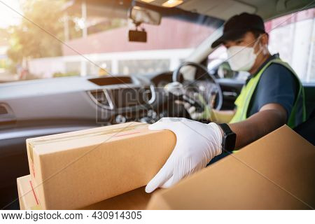 A Delivery Man Holding Credit Card Reader Is Picking Up A Box In A Friend's Car To Deliver It To A C