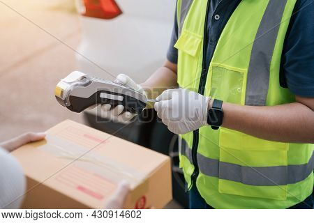Close Up Hand Of Delivery Man Using A Credit Card Reader While Delivering Products To Customers At H
