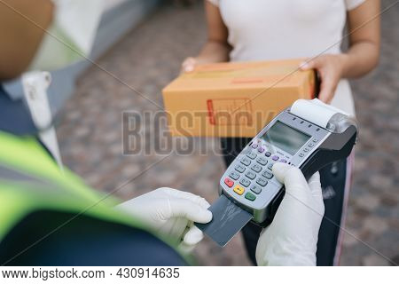 Close Up Hand Of A Delivery Man Using A Credit Card Reader While Delivering Products To Customers At