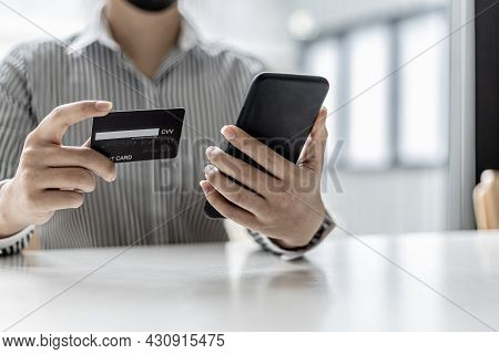 Woman Holding A Smartphone And A Credit Card, She Is Filling Out Her Credit Card Information To Pay