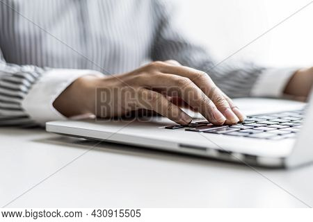 A Woman Typing On A Laptop Keyboard, She Is Filling Out Her Credit Card Information To Pay For An Or