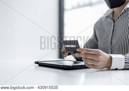 A Woman Holding A Credit Card And Touching A Tablet, She Is Filling Out Her Credit Card Information