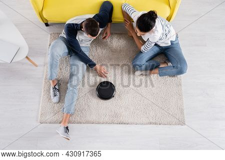 Overhead View Of Multiethnic Couple Sitting Near Robotic Vacuum Cleaner
