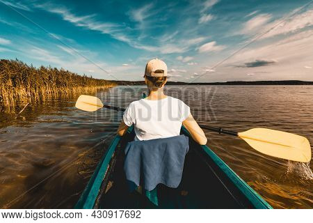 Girl Kayaking On The Lake At Sunset - View From Behind Her Back