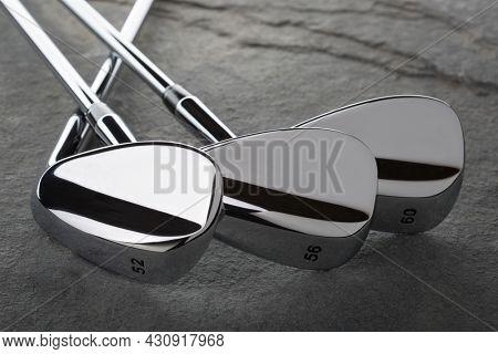 Chrome Golf Club Wedge Iron Set On Rock Surface.