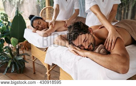 Couple Massage At Spa Resort. Beautiful Couple Getting A Back Massage Outdoor, Romantic Weekend And