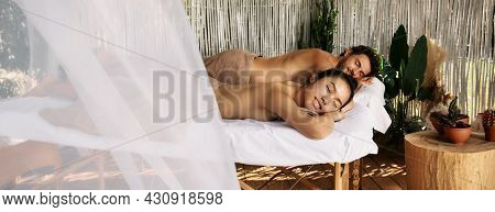 Multi-ethnic Couple Having Relax During Back Massage Lying With Eyes Closed On Massage Tables At Rom