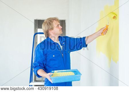 Man Painting Wall In Yellow Color With Roller. Renovation, Repair And Redecoration Concept